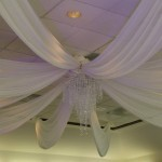 ivory ceiling drape with crystal chandelier